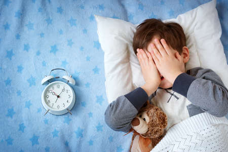 six years old child sleeping in bed on pillow with alarm clock and a teddy bear