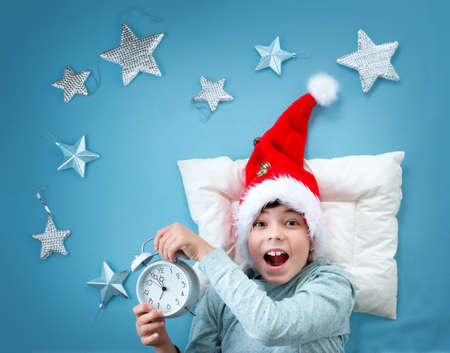 child smile: Happy child on blue blanket in red hat. Cute boy in christmas cap with alarm clock