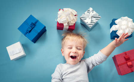 baby open present: Happy child on blue blanket. Cute boy with many presents