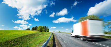 route goudronnée sur le champ de pissenlit avec un petit camion. camion de déménagement sur la journée ensoleillée Banque d'images
