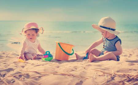 babyboy: Babygirl and babyboy sitting on the beach in straw hats