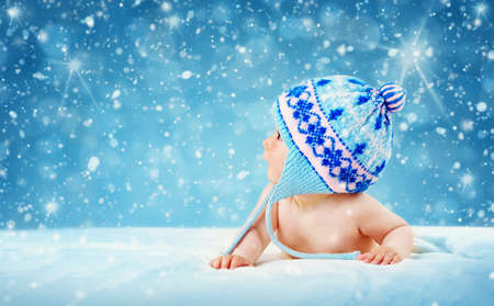 baby blue: Eight month old baby in knitted winter hat lying on soft blanket with blue background and falling snow