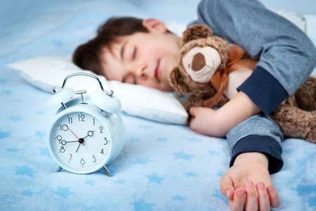 6 Jahre altes Kind schlafend im Bett auf Kissen mit Wecker