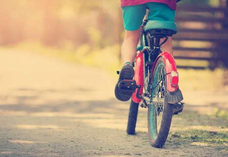 ребенок на велосипеде по асфальтовой дороге ранним утром