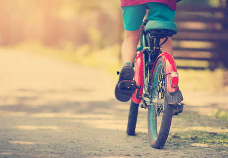 child on a bicycle at asphalt road in early morning Stock Photo
