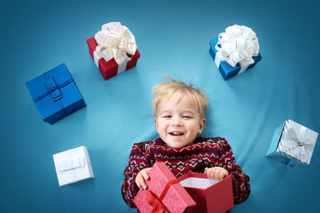 Happy child on blue blanket. Cute boy with many presents