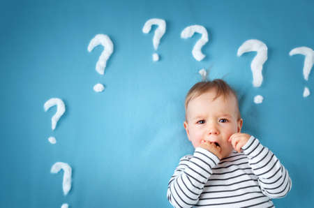 little boy lying on blue blanket with lots of question marks