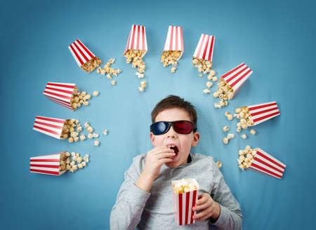 子 3 d メガネに青色の背景に横たわっているとテレビを見て