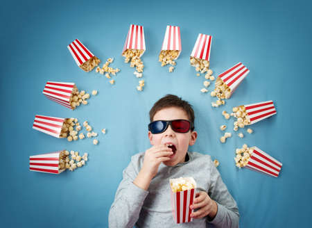 Child lying on blue background in 3d glasses and watching tv
