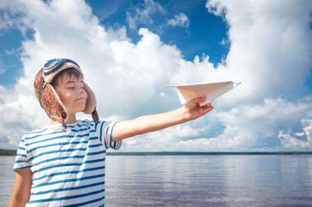 boy playing with a paper plane in aviator hat 版權商用圖片 - 71054301
