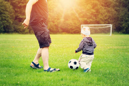Little boy playing football on the field with gates Stock Photo - 71691159
