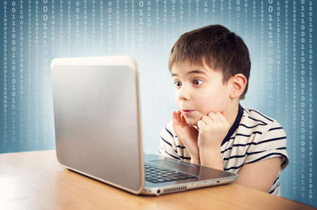 online safety: seven years old child sitting with a laptop Stock Photo