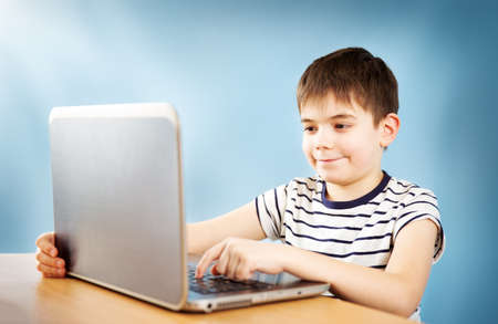 seven years old child sitting with a laptop Stock Photo