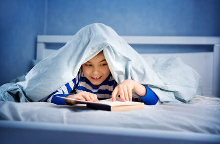 boy lying in bed with a book