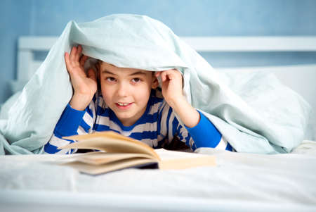 bedtime story: boy lying in bed with a book