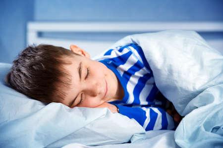 8 years old: Boy sleeping in bed in pajamas