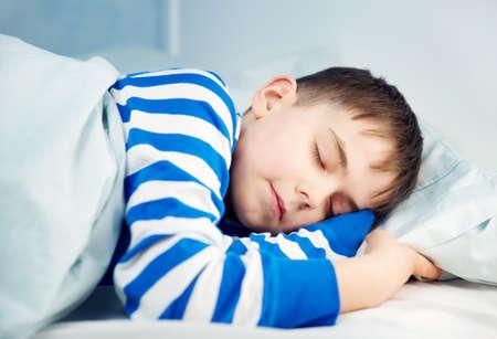 Boy sleeping in bed in pajamas