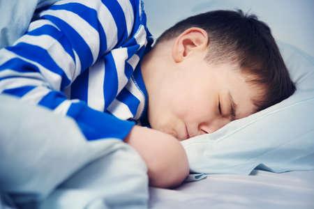 Garçon dormir dans le lit en pyjama Banque d'images