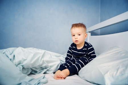 ベッドに座っている眠い少年