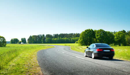 Car on asphalt road in beautiful spring day