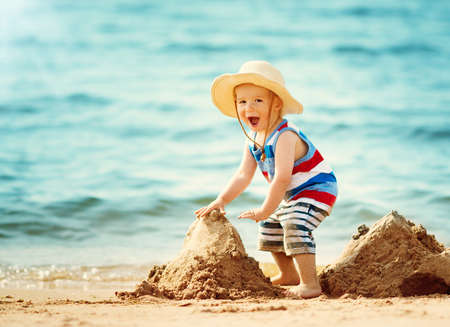 little boy walking at the beach in straw hat