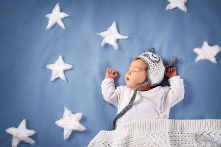 Cute bebé recién nacido tumbado en la cama. Niño de 2 meses en sombrero de búho durmiendo en manta azul