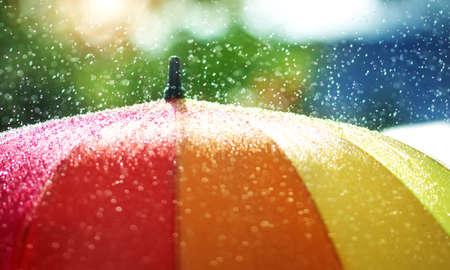 Rain drops falling onto umbella with rainbow colour