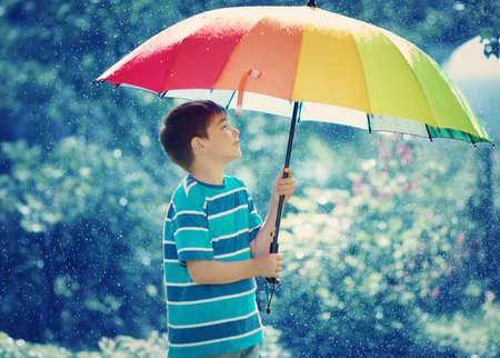 niños riendose: Niño caminando en tiempo lluvioso Foto de archivo