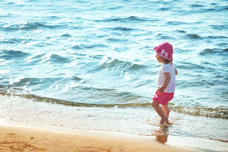 Baby girl is walking on the beach
