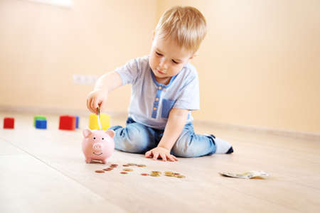 two years old child sitting on the floor and putting money into a piggybank