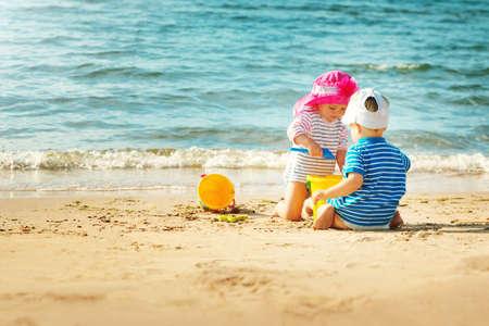 Babygirl and babyboy sitting on the beach Stock Photo