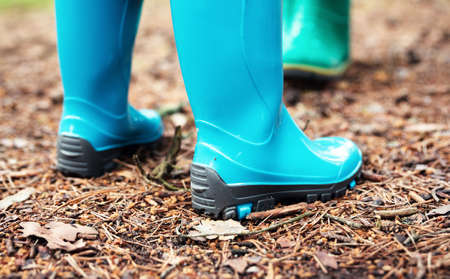 Children standing in wellies in the forest