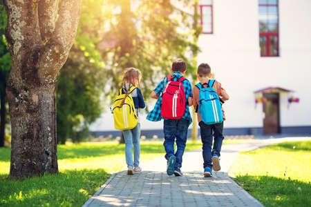 Children with rucksacks standing in the park near school