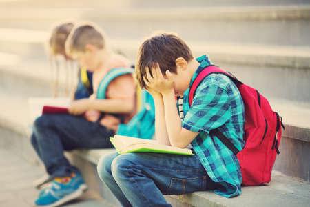 Children with rucksacks sitting on the stairs near school. Stok Fotoğraf