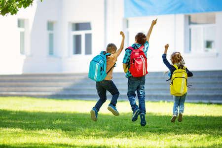 학교 근처 공원에서 점프하는 배낭과 어린이 스톡 콘텐츠
