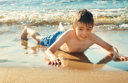 Child lying on the beach with swimming mask and flippers. Stok Fotoğraf