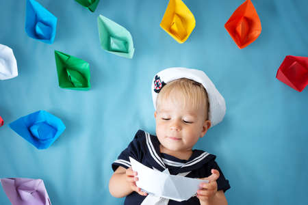 A boy playing in sailor hat with paper ships on blue Stok Fotoğraf