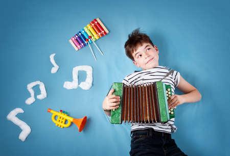 xilofono: Niño en azul manta de fondo con acordeón