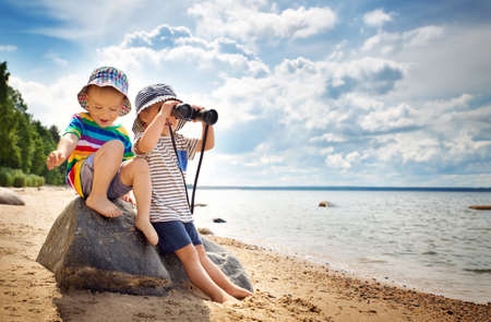 Babygirl and babyboy sitting on the beach Stock Photo