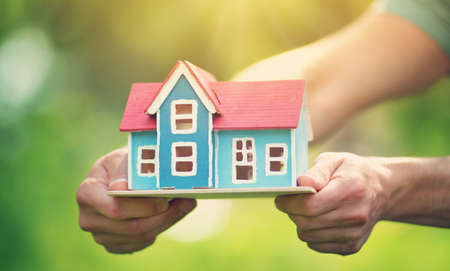 man hands holding wooden house Stock Photo