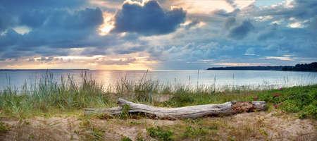 Log in op het strand bij zonsondergang