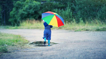 Child walking in wellies in puddle on rainy weather Stock fotó