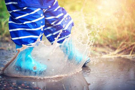 雨の水たまりに長靴で歩く子 写真素材 - 83433314