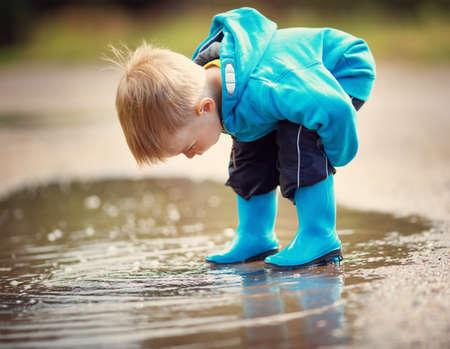 雨の水たまりに長靴で歩く子 写真素材