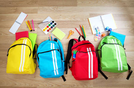 white wood floor: Colourful children schoolbags on wooden floor. Backpacks with school accessories Stock Photo