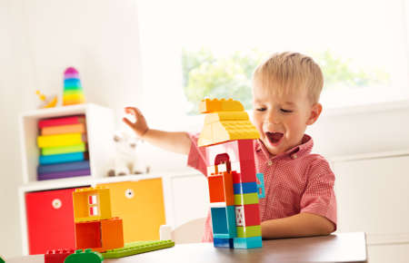 Little child playing with blocks photo