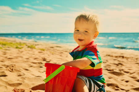 little boy smiling at the beach photo