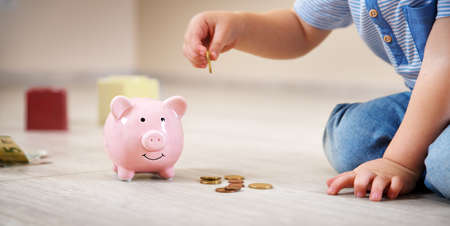 two years old child sitting on the floor and putting a coin into a piggybank photo