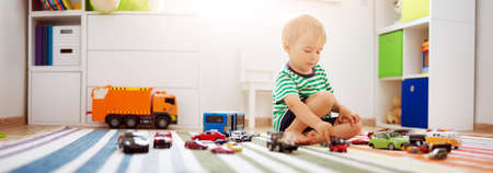Little child playing with toy cars Imagens