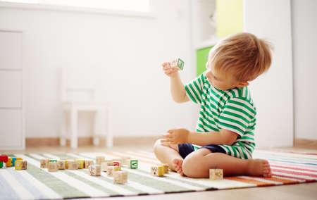 木製キューブで床に座っている 2 歳児